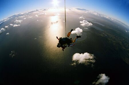 Man and woman skydiving in tandem from an aircraft photo