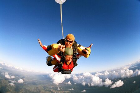 Man and woman skydiving in tandem from an aircraft