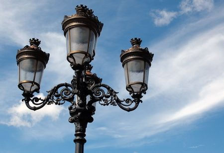 Old fashioned street lamp which uses oil with sky as background. photo