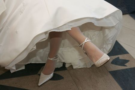 Bride in traditional white wedding dress crossing her legs, seen from waist down. Stock Photo - 2925030