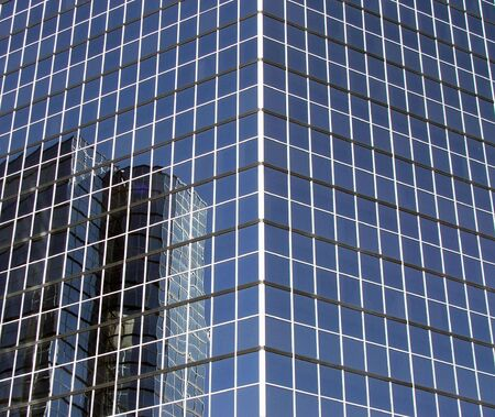 Skyscraper reflected in office windows of building. Stock Photo - 2925042