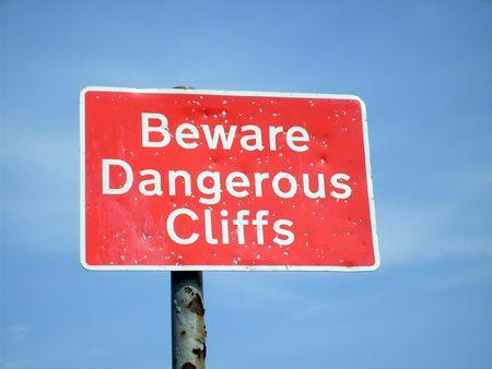 Beware Dangerous Cliffs sign, blue sky background. photo