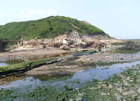 River leading to seashore filling rock pools in beach scene. photo