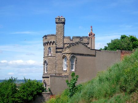 battlements: Historic house shaped like a castle with battlements and turrets.