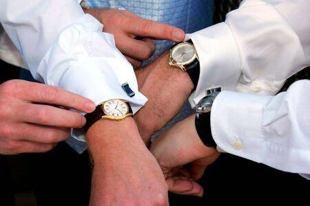 coordinacion: Tres personas comprobando el tiempo en sus relojes.
