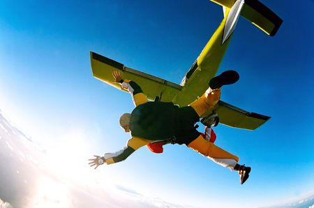 midair: Tandem skydiver in action parachuting, seen in mid air position.