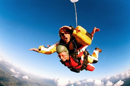 Tandem skydiver in action parachuting, seen in mid air position. photo