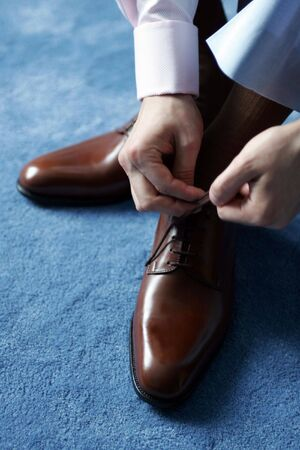 Businessman tying his shoes as he gets dressed for work. photo