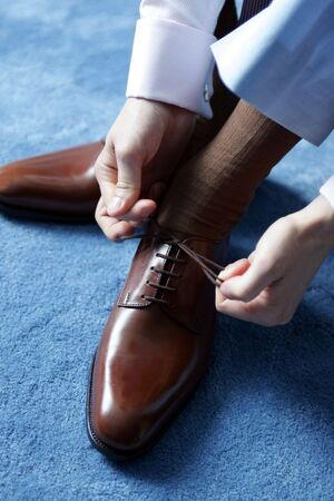 he: Businessman tying his shoes as he gets dressed for work.