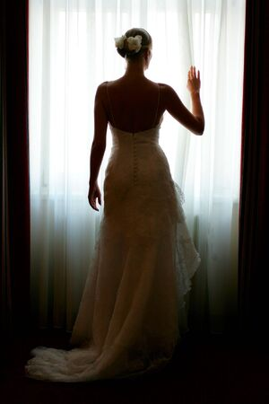peering: Silhouette of a beautiful bride in a traditional white wedding dress, stood by window.