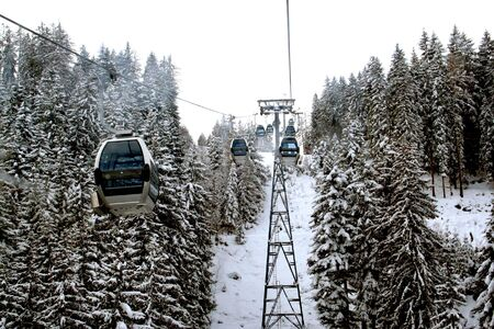 Details of ski lift in Swiss Alps over forest. photo