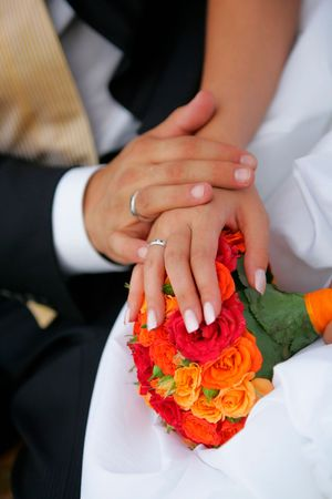 Close up portrait of newlywed man and wife holding hands over bouquet of colorful flowers and petals.