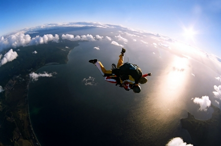 sea sports: Portrait of two tandem skydivers in action parachuting through the air. Stock Photo