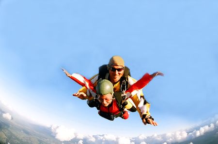 skydive: Portrait of two tandem skydivers in action parachuting through the air. Stock Photo
