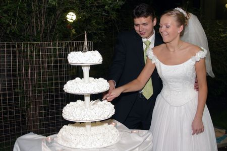 look pleased: Beautiful bride in white cutting wedding cake with handsome groom Stock Photo