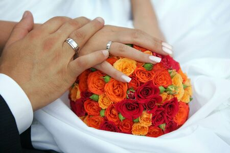 Newlywed couple holding hands on wedding dress and bouquet