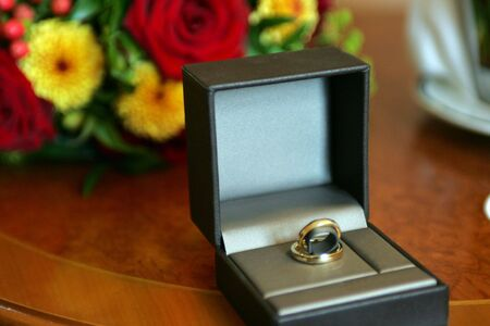boxed: Brides engagement Ring pictured in a box next to bouquet