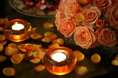 dimly: Close up of table decorated with burning candles and flower petals, romantic scene. Stock Photo