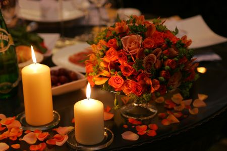 mood: Close up of table decorated with burning candles and flower petals, romantic scene. Stock Photo
