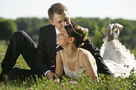 Newlywed couple kissing in field in countryside.
