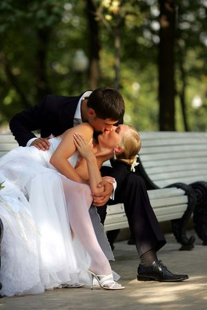 Newlywed couple kissing on park bench. photo