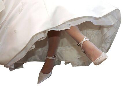 crossing legs: Bride in traditional white dress crossing her legs.