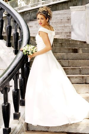 Beautiful bride in white dress stood on steps. Stock Photo - 3931363