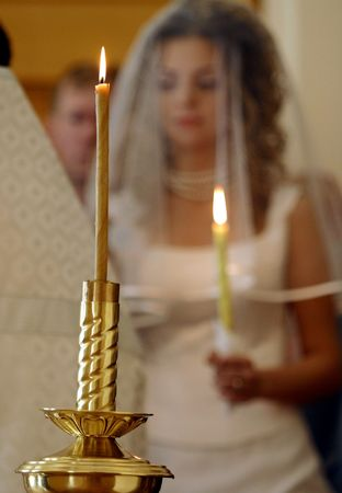 Bride walking down aisle in church, lighted candle in foreground. photo