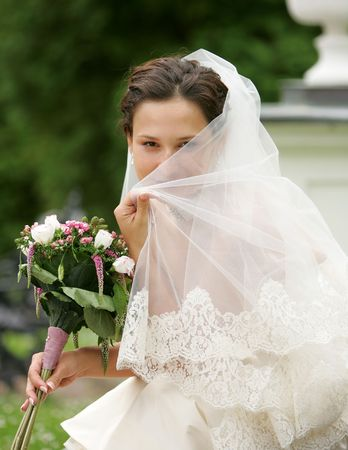 Bride hiding behind her veil, smiling happily and coyly. Stock Photo - 3931359