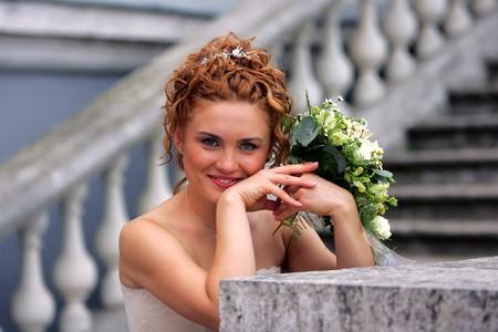 Half body portrait of smiling auburn bride holding wedding bouquet. photo