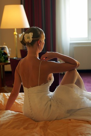 Rear view of blond bride sat on bed on wedding day with lit lamp. photo