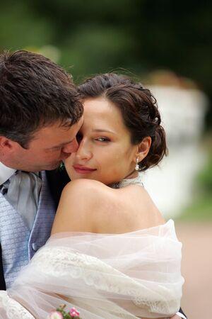 Close up portrait of newlywed caucasian couple kissing. photo