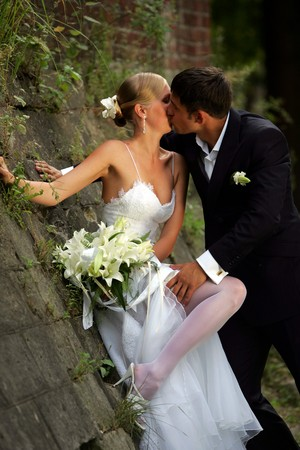Kissing newlywed couple leaning against wall in countryside. photo