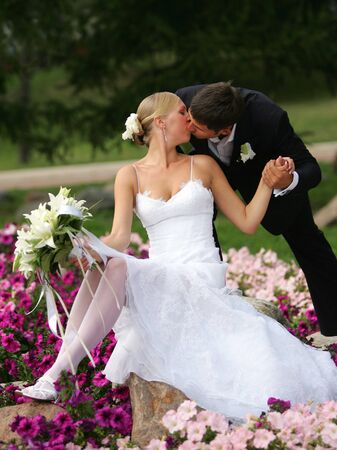 Newlywed couple kissing on flower bed in countryside. Stock Photo