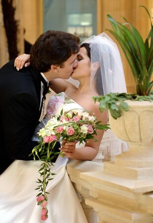 Newlywed couple kissing passionately indoors, bride holding bouquet.