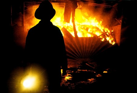 incendiary: Rear view of fireman shining torch on burning building. Stock Photo