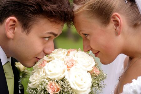 Close up of smiling newlywed couple touching foreheads over bouquet of flowers. photo