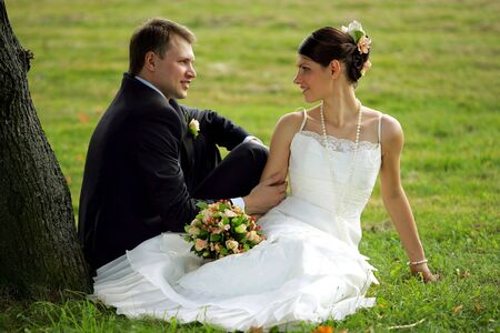 Newlywed couple sat in field under tree romancing. photo