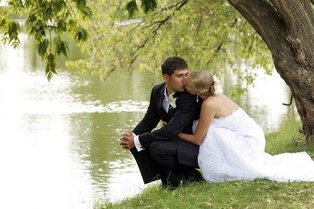Newlywed couple kissing by lake, pretty bride and handsome groom in love.