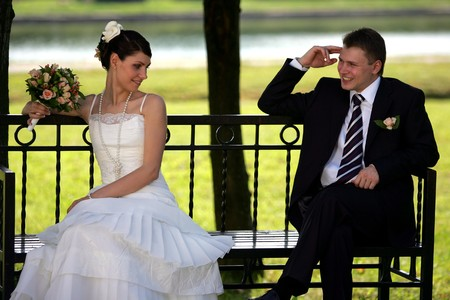coy: Newlywed couple sat on park bench, smiling groom and coy bride with bouquet.
