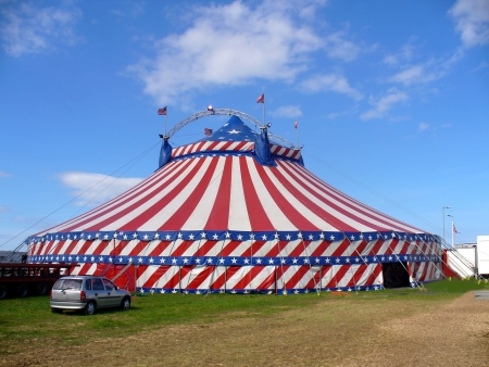 Exterior of American circus marquee tent in stars and stripes of American flag, blue sky background.
