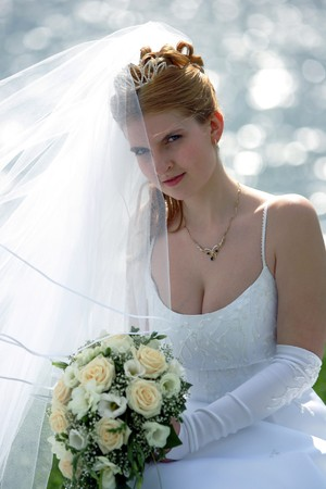 Half body portrait of smiling bride with veil and bouquet sat in front of lake.