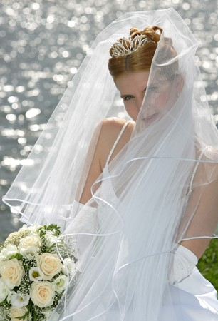 Young smiling bride holding bouquet hiding behind veil, lake in background. photo