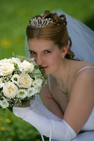 Beautiful young bride holding bouquet of flowers and smiling, green background. photo