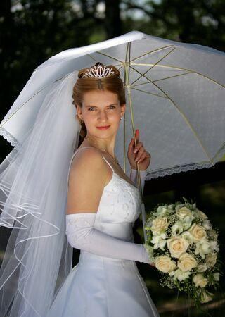 Half body portrait of smiling bride holding bouquet under parasol. photo