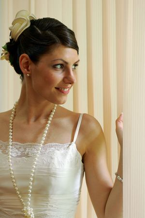 Smiling young bride in traditional white wedding dress peeping through blinds. Stock Photo - 4593784