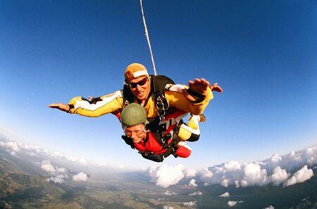 spadochron: Tandem skydivers uśmiechnięte w połowie poisition ponad Cloudscape powietrza i ziemi. Zdjęcie Seryjne