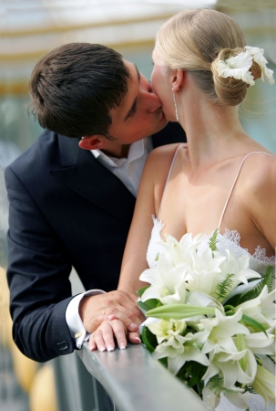 Half body portrait of attractive newlywed couple kissing.