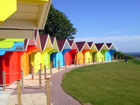curving lines: Scenic view of colorful beach chalets with ocean in background, Scarborough, England.