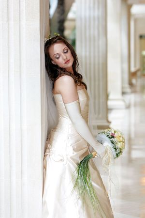 leans: Pretty young adult bride wearing wedding dress and holding bouquet leaning on marble column, thoughtful expression.
